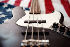 Vintage bass guitar on american flag background Stock Photos