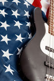 Vintage bass guitar on american flag background Stock Images