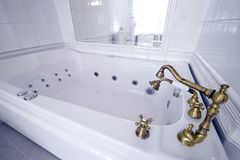 Vintage bathtub. Elegant, vintage bathtub with golden faucets Royalty Free Stock Photo