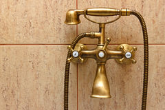 Vintage bathtub faucet and ceramic tiles. In background.Retro bronze look Royalty Free Stock Image