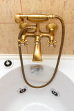 Vintage bathtub faucet and ceramic tiles. In background.Bathtub with jacuzzi.Retro bronze look Royalty Free Stock Photos