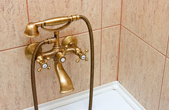 Vintage bathtub faucet and ceramic tiles. In background.Retro bronze look, perspective view Royalty Free Stock Photo