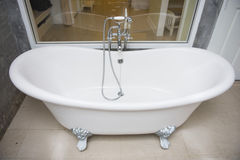 Vintage bathtub with faucet and shower in bathroom. Interior Royalty Free Stock Photo