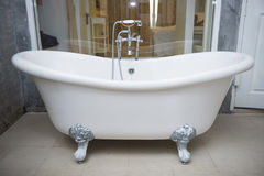 Vintage bathtub with faucet and shower in bathroom. Interior Stock Photo