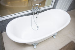 Vintage bathtub with faucet and shower in bathroom. Interior Royalty Free Stock Photos