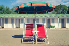 Vintage beach chair, ubrella and hut. Royalty Free Stock Image