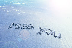 Vintage beach miss you handwriting. Vintage sunny miss you handwriting sign on sea sand with wave. Blue color filter used Stock Photography