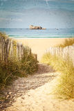 Vintage Beach Postcard. Entrance to a sandy beach using a fence lined pathway. This has a vintage postcard texture and feel Stock Image