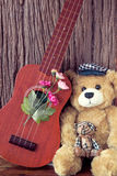 Vintage bear toy with ukulele. On wooden backgrounds Stock Photography