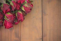 Vintage beau Fermez-vous des roses rouges sur un fond en bois Photographie stock libre de droits