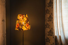 Vintage Bedroom floor lamp glowing orange in a corner of a room Royalty Free Stock Images