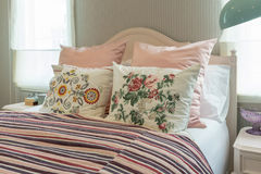 Vintage bedroom with flower pillows and pink striped blanket. Vintage bedroom interior with flower pillows and pink striped blanket on bed Royalty Free Stock Photos