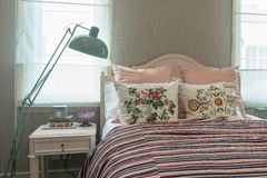 Vintage bedroom with flower pillows and pink striped blanket. Vintage bedroom interior with flower pillows and pink striped blanket on bed Royalty Free Stock Images