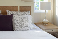 Vintage bedroom interior with flower pillows and decorative lamp Royalty Free Stock Images