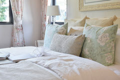 Vintage bedroom interior with flower pillows and decorative table lamp Royalty Free Stock Images