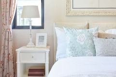 Vintage bedroom interior withreading lamp and picture frame on bedside table Royalty Free Stock Photos