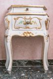 Vintage bedside table. With golden decoration from Venice, Italy royalty free stock photo
