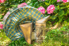 Vintage beekeeping protective hat and smoker. In the garden, retro feeling royalty free stock photos