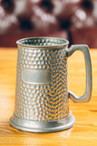 Vintage beer iron mug on table. Metal vintage beer iron mug on table Royalty Free Stock Photo
