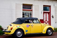 Vintage Beetle Convertible Car. Vintage yellow convertible beetle with flower stickers  parked outside a white building with red door Stock Photos