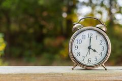 Vintage bell clock on a wooden fence with fall foliage in the ba Royalty Free Stock Images