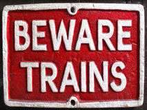 Vintage beware trains enamel sign. Old vintage red retro distressed railway enamel metal sign with text, beware trains Stock Photos