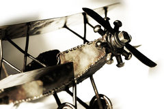 Vintage Bi-Plane Model (sepia, close-up, shallow focus). Close-up of a replica vintage model biplane, with shadow on white - represents transportation, travel stock photography