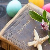 Vintage Bible with Lent Cross, Easter Eggs, and Flowers in Closeup Flat Lay from Above. Vintage Leather Bible with grass cross, flowers, Colorful Easter Eggs on Stock Photography