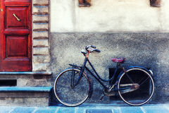 Vintage bicycle against the wall in front of the door to the hou Royalty Free Stock Images