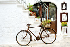 Vintage bicycle against a wall in white city Ostuni, Apulia, Italy - artistic picture italian style concept Royalty Free Stock Photo