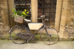 Vintage bicycle with bunches of flowers. Parked in the street in Oxford, United Kingdom. This bicycle was used like restaurant signal Stock Image