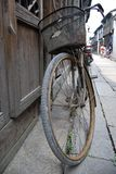 VINTAGE BICYCLE IN CHINA. An old vintage bicycle resting agianst a wooden wall in a small village in China Royalty Free Stock Photo