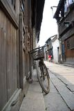 VINTAGE BICYCLE IN CHINA. An old vintage bicycle resting agianst a wooden wall in a small village in China Stock Image