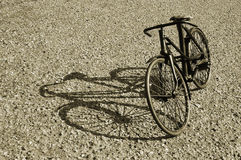 Vintage bicycle. A DSLR photograph of a vintage bicycle on an asphalt road with shadow Stock Image