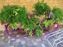 Vintage bicycle equipped with baskets of flowers and leaves Stock Image
