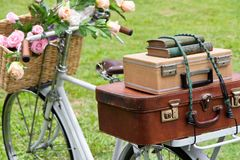 Vintage bicycle on the field. With a basket of flowers and bag Stock Photo