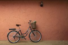 Vintage bicycle standing near the red brown wall. Vintage bicycle with flower basket leaning against rustic wall stock image
