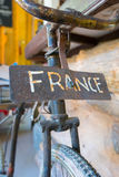 Vintage bicycle with France sign in the front. Retro vintage obj. Retro vintage bicycle with old rusted signs saying France inside a room. Selective focus stock photography