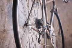 Vintage bicycle hang on wall. Closeup Bicycle gear, disk brake, metal chain rings of vintage mountain bicycle hanging on old wall. Antique color process. Sport Royalty Free Stock Photography