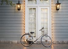 Vintage Bicycle. Lay on Classic style house entrance grey walls, white wooden door and windows decorates with illuminate royalty free stock images