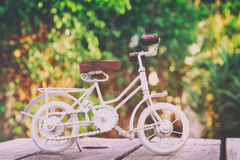 Vintage bicycle miniature toy waiting outdoors. In the garden. Filtered and toned stock images