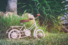 Vintage bicycle miniature toy waiting outdoors. In the garden. Filtered and toned royalty free stock photography