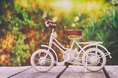 Vintage bicycle miniature toy waiting outdoors. In the garden. Filtered and toned royalty free stock photo