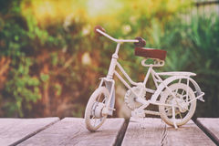 Vintage bicycle miniature toy waiting outdoors. In the garden. Filtered and toned stock photo