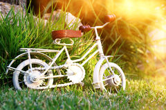 Vintage bicycle miniature toy waiting outdoors. In the garden at sunset light royalty free stock images