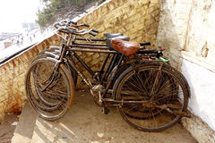 Vintage Bicycles. Three vintage fixed gear bikes stacked up against an old brick wall high up on the ghats of Varanasi India Stock Photos