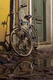 Vintage bike tied to the downpipe on cobbled street of old town Royalty Free Stock Photos