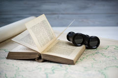 Vintage binoculars and antique open book on the old map Royalty Free Stock Photos