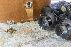 Vintage binoculars, leather case and compass resting on an old w Stock Photos