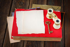 Vintage binoculars on red ancient book with blank page for text. nostalgic vintage background Stock Photography